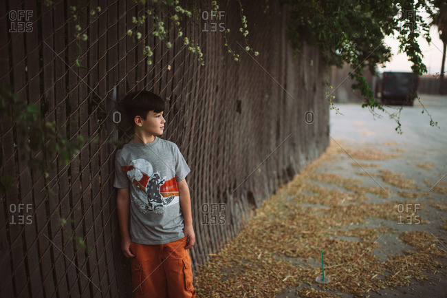 Young boy leaning against chain link fence with wooden slats