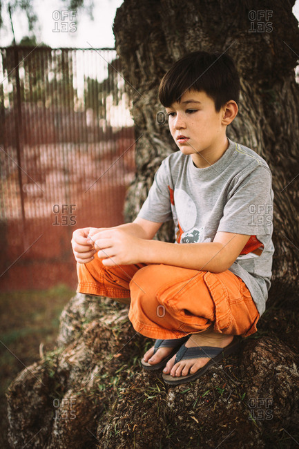Young boy sitting on tree trunk