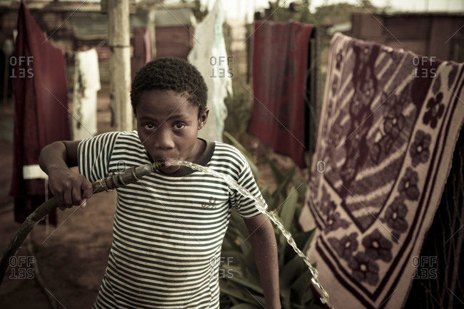 Young black boy looking at camera, drinking water from a hose pipe