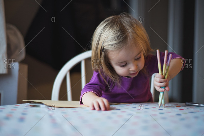 Little girl holding colored pencils while sitting at the table
