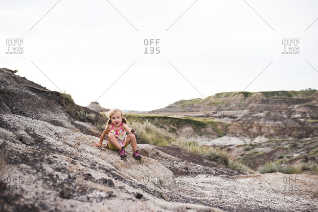 Little girl sitting on a rocky hillside