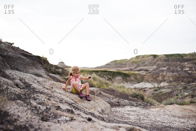 Girl sitting on a hillside holding a rock