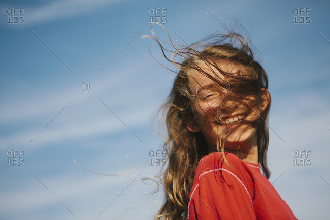 A smiling nine year old girl, with the wind blowing her hair over her face.