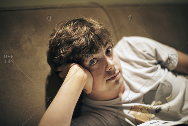 A young man lying on a sofa, resting his head on his elbow and looking at the camera.