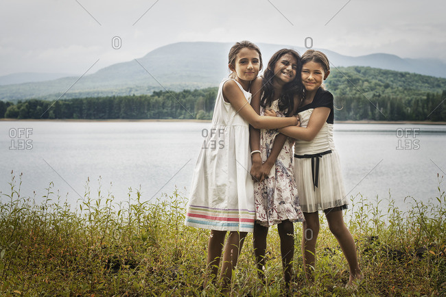Three young girls standing by the side of a lake, hugging each other.