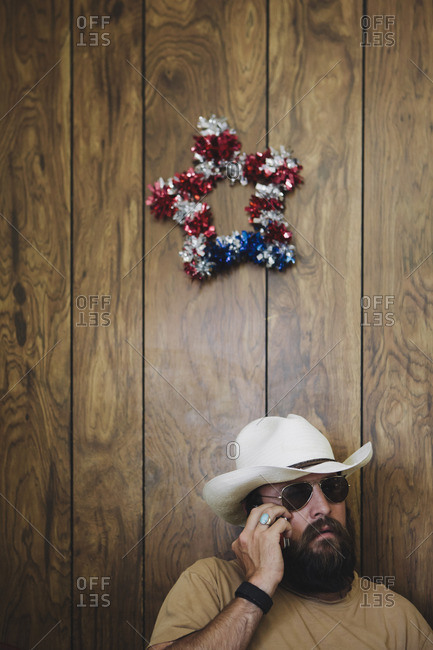Man with long beard and cowboy hat talking on cell phone.