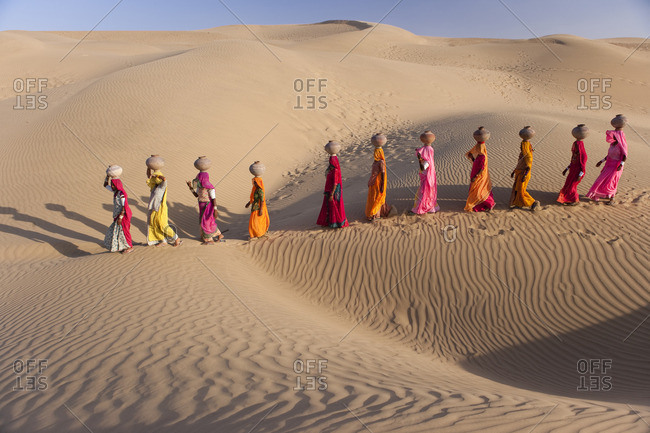 Women bear the responsibility of fetching water from the sparse wells within Rajasthan's vast Thar Desert. Trekking up the side of a sand dune, women expertly balance large clay water vessels atop their heads. Rajasthan, India
