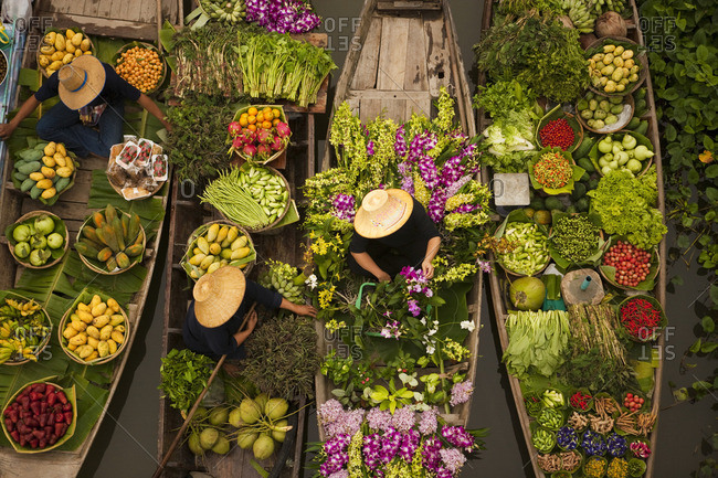Aerial view of a floating market on a canal in Bangkok, local boats laden with fresh food, moored close together.