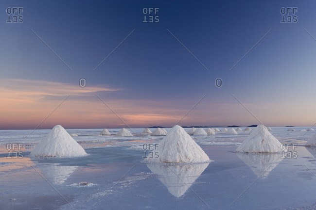 The salt pans of Salar de Uyuni, with shallow water and mineral deposits. White salt granules raked into heaps.