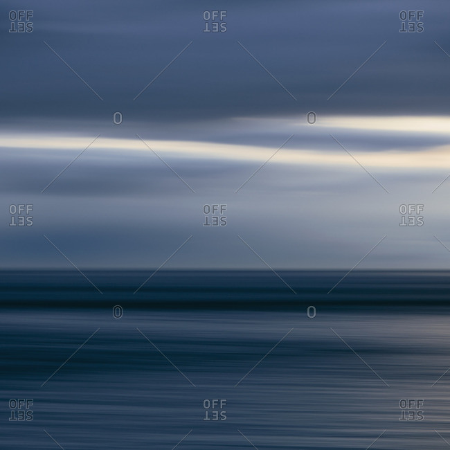 The sea and sky over Puget Sound in Washington, USA. The horizon with light cloud layers above. Gathering storm clouds.