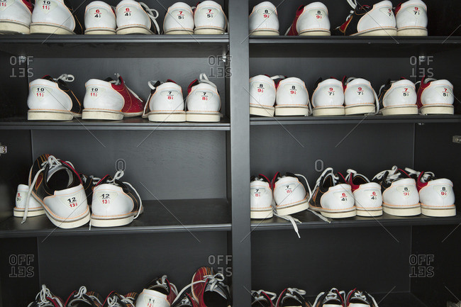 Pairs of bowling shoes arranged on shelves against the wall  in a bowling alley.