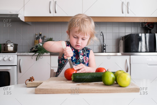 Child slicing a tomato on a cutting board