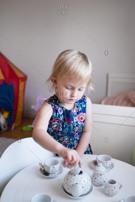 Little girl lifting the lid off a tea pot at a tea party