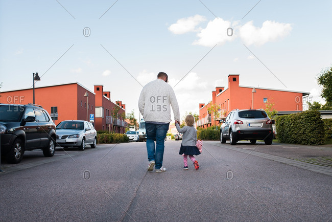 Father and daughter holding hands while walking down the street