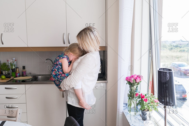 Mother holding her daughter who has her head in her hands