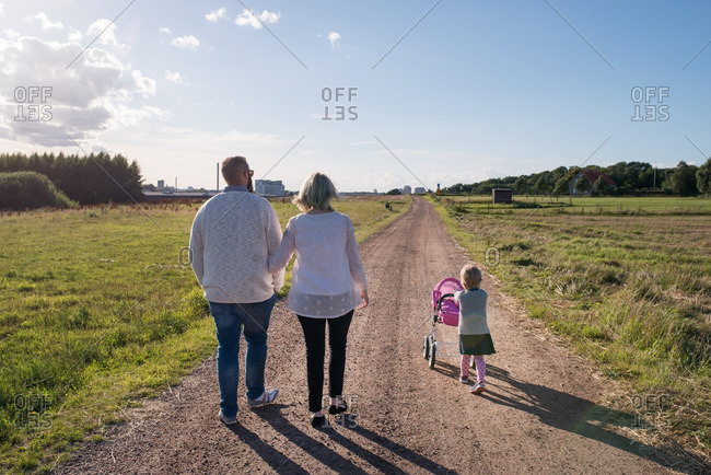 Family walking together on a dirt road while little girl pushes a toy baby carriage