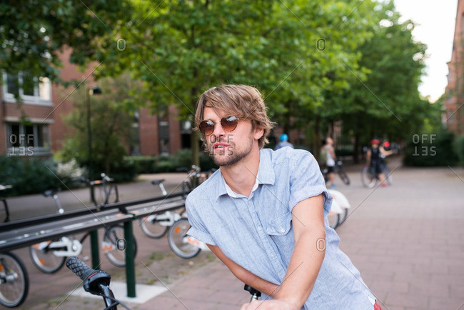 Portrait of a young man getting off a bicycle
