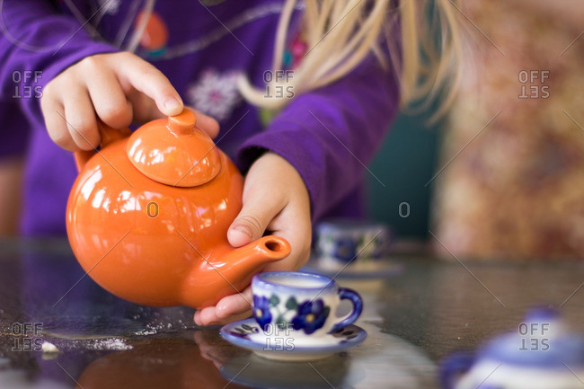 Close-up of child pouring tea