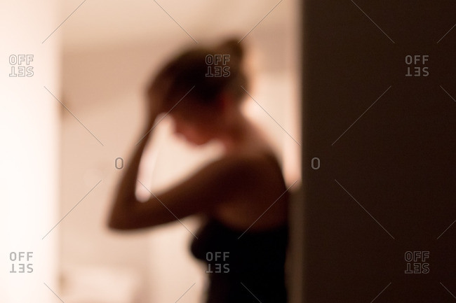 Blurry woman with hand on forehead