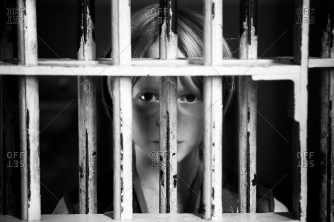 Boy looking through bars - Offset