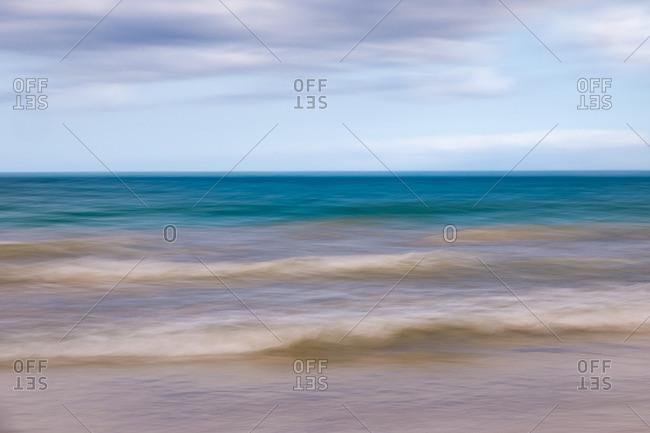 Blurred image of waves crashing on beach