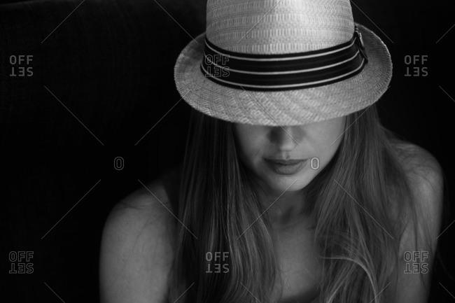 A woman hiding beneath a fedora