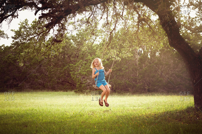 Girl on tree swing during golden hour