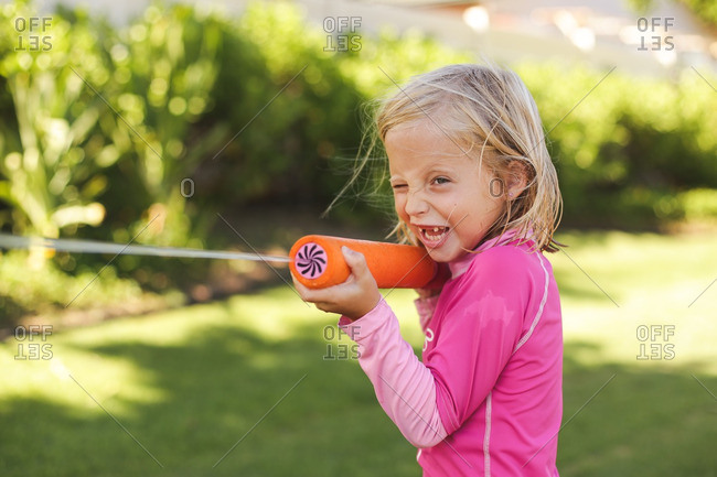 Girl playing with a squirt gun
