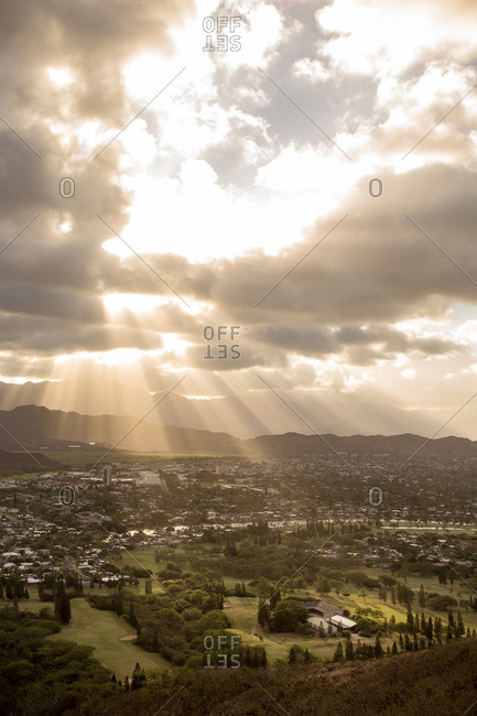 Sunbeams through clouds over valley town