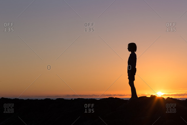 Silhouette of boy by ocean at sunset