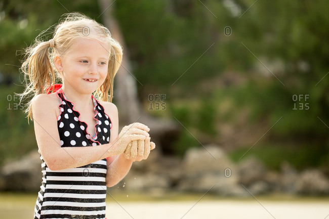 Girl in pigtails holding beach sand