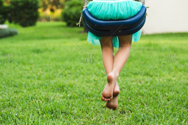 Girl with bare feet on swing