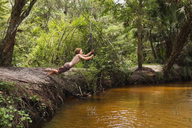 Boy leaping on forest rope swing