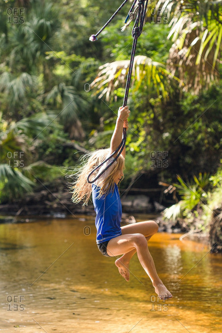 A girl on stream rope swing