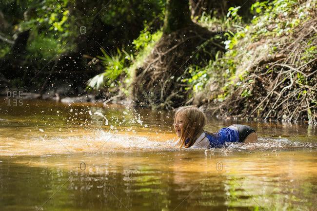 Girl splashing in rural creek