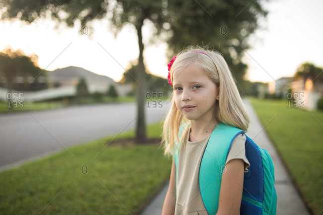 Girl with backpack on a sidewalk
