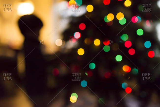 Silhouette of a boy decorating a Christmas tree