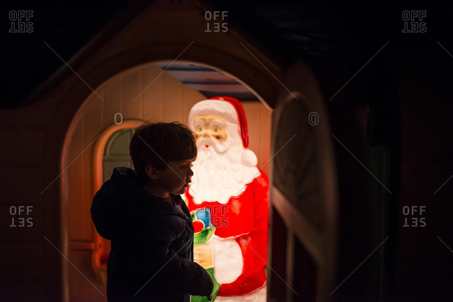 Boy visiting an illuminated plastic Santa Claus in a toy house at night