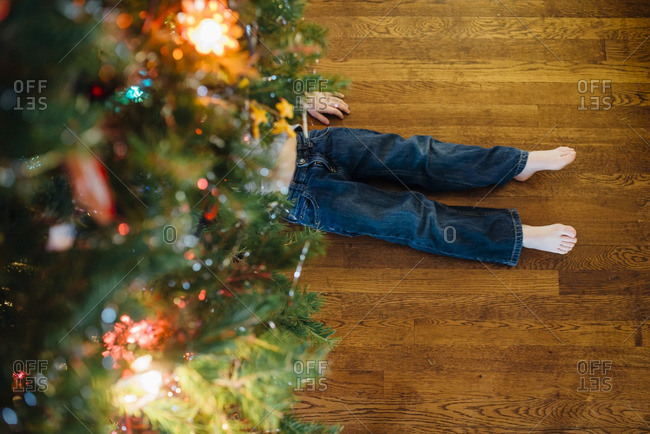 Child's bare feet sticking out from under a Christmas tree