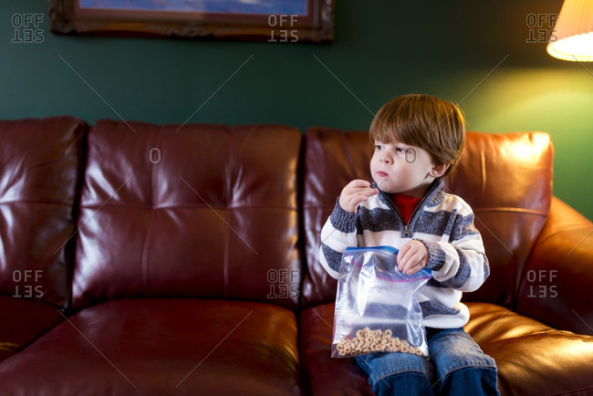 Boy sitting on a couch eating cereal from a plastic bag