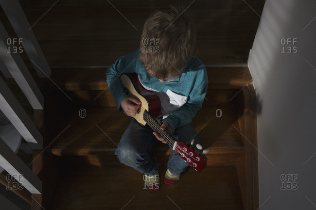 Boy playing a ukulele on the stairs