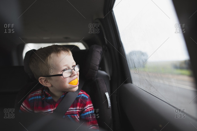 Boy riding in the backseat of a car with an orange peel in his mouth