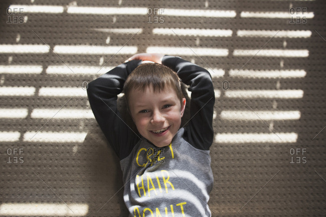 Boy standing against a wall with his hands above his head smiling