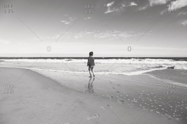 Boy walking along a beach