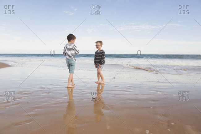 Two boys standing on the beach together