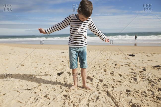 Boy standing on a sandy beach