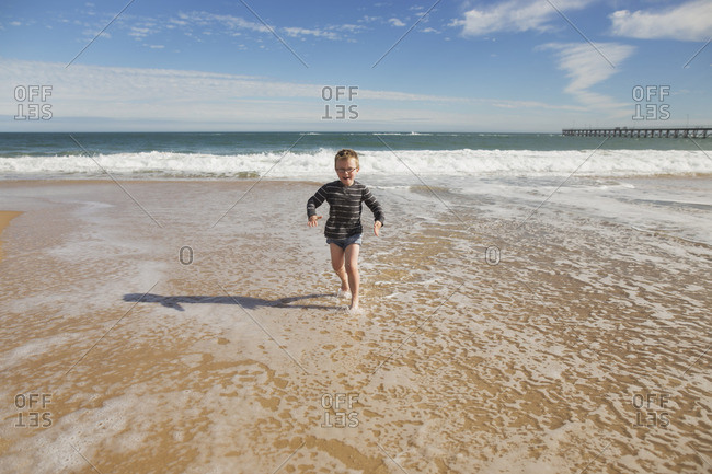 Boy running through the surf on a beach