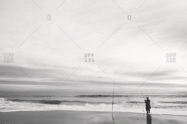 Man fishing along an empty stretch of beach