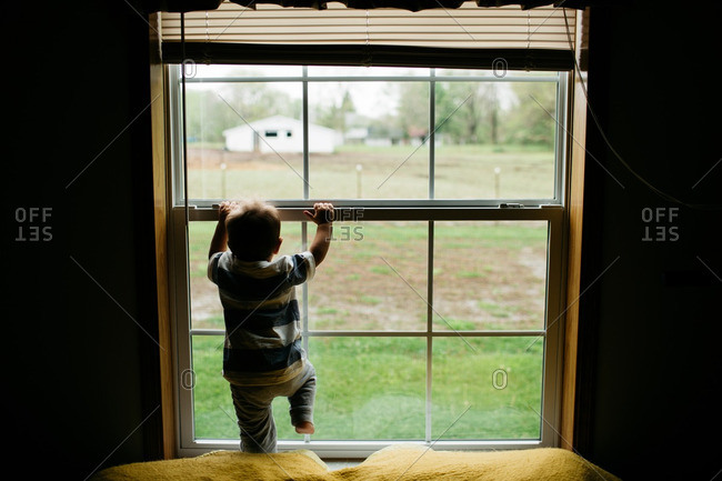 Boy climbing on his bedroom window