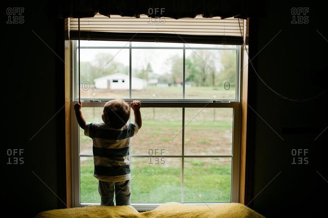 Boy grasping his bedroom window